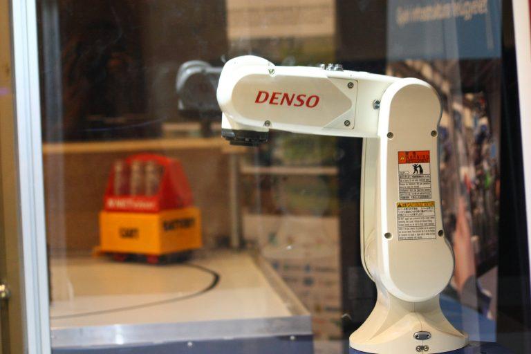Ipari robot    Az adatgyűjtés és optimalizáció mellett az automatizáció az Ipar 4.0 kulcs eleme. A Delta Robotics által forgalmazott DENSO ipari robot, amely megtekinthető a TK-ban, egy kifejezetten ipari környezetre tervezett, nagy sebességgel és pontossággal működő kooperatív ipari robot. A robot védett géptérben működik, por-, füst-, tűz-, pára-, és vízvédelemmel is el van látva. A szcenárió részeként egy ragasztó adagoló fejjel műküdik, a demonstráció kedvéért a valós sebességének körülbelül 20%-val.   Együttműködő partner: Delta Robotics