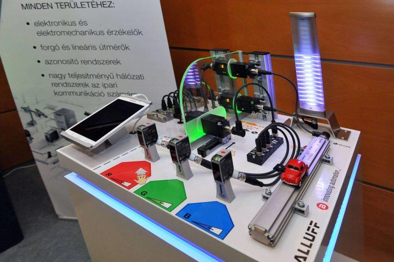 Szenzorok alkalmazása   Az Ipar 4.0 megoldások alapja a fizikai rendszerekből származó adatok gyűjtése, továbbítása a digitális rendszerek fele. A szcenárió a Balluff cég által Magyarországon gyártott ipari szenzorokból mutat be néhányat - RFID olvasók, optikai közelítés érzékelők, digitális kamera. A szenzorok jeleit az ipari szabványnak tekinthető IO-Link rendszer gyűjti össze és továbbítja. A mért adatokat korszerű, digitális toronylámpákon jelenítjük meg.    Együttműködő partner: Balluff